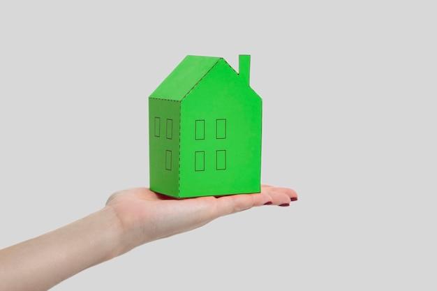 Ludzka kobieta ręka trzyma i pokazuje zielony papier dom model. kryty strzał studio, na białym tle na szarym tle.