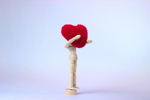 Ludzka lalka z wielkim czerwonym sercem w dłoniach na ładnym kolorowym tle. koncepcja miłości