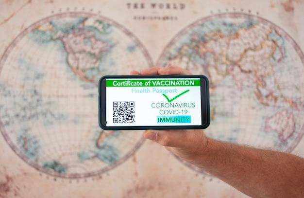 Ludzka męska ręka trzymająca telefon komórkowy z zieloną kartą paszport świadectwo zdrowia szczepienia