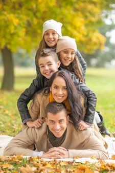 Ludzka piramida pięciu leżących członków rodziny na zewnątrz w jesienny dzień.