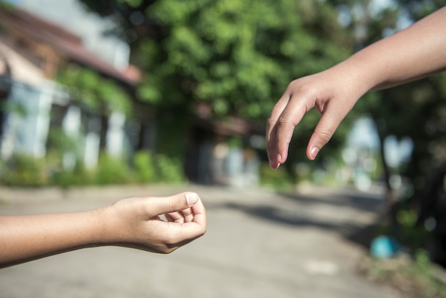 Ludzka ręka daje pomocną dłoń z rozmytym tłem