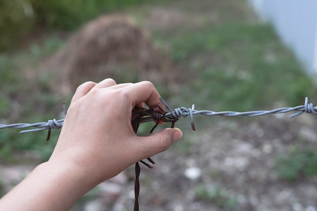 Ludzka ręka dotyka starego i starzejącego się drutu kolczastego, rozmyte światło wokół