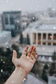 Ludzka ręka łapie płatki śniegu.
