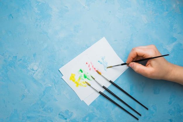 Ludzka ręka malowanie na białej kartce z pędzlem na niebieskim tle pastelowych