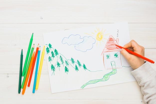 Ludzka ręka maluje ręka rysującego rysunek z czerwonym filcowym piórem