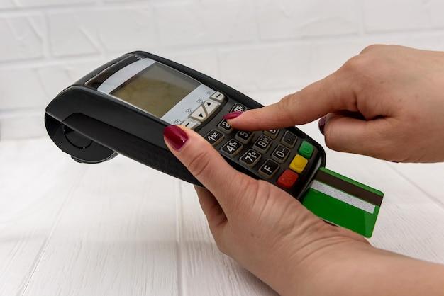 Ludzka ręka naciskając przyciski na terminalu bankowym