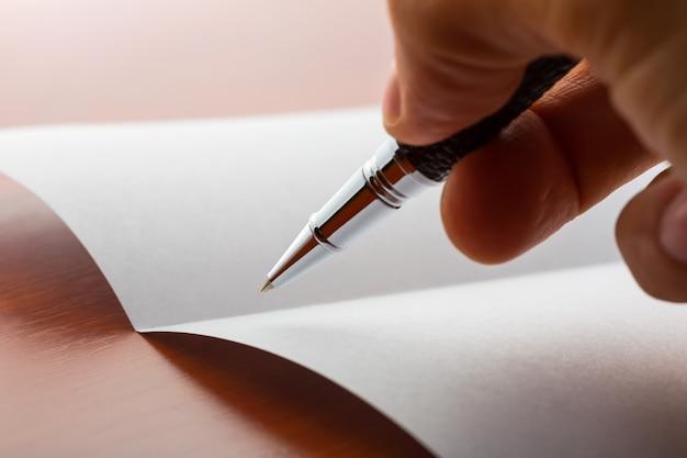 Ludzką ręką pisania na papierze za pomocą długopisu