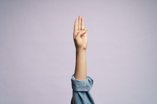 Ludzka ręka pokazuje trzy palce na białym tle.