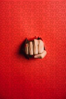 Ludzka ręka rozrywająca czerwony papier słowem covid-19