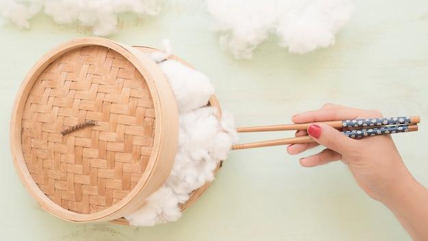 Ludzka ręka trzyma bawełnę z chopsticks od parostatku