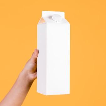 Ludzka ręka trzyma białą tetra paczkę nad żółtym tłem