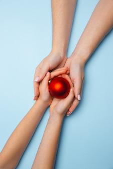 Ludzka ręka trzyma bombkę na białym tle na niebieskim tle. koncepcja uroczystości, święta, rodzina, komfort w domu, ferie zimowe, sylwester. prezent na szczęśliwe czasy.