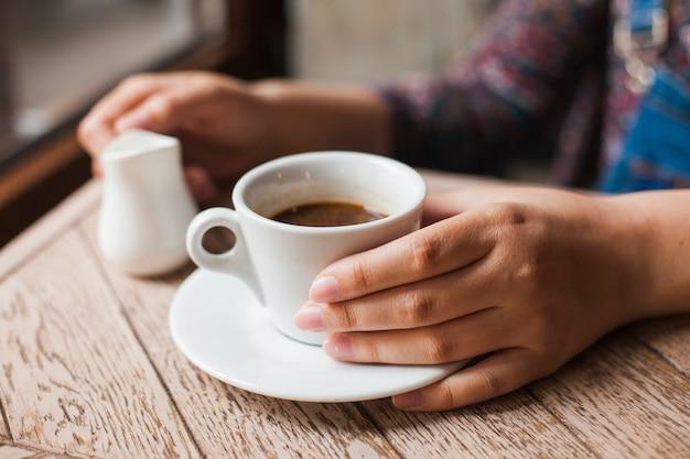 Ludzka ręka trzyma czarną filiżankę i mleko dzban