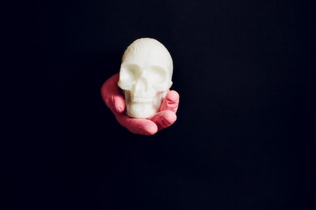 Ludzka ręka trzyma czaszkę. halloweenowy grunge