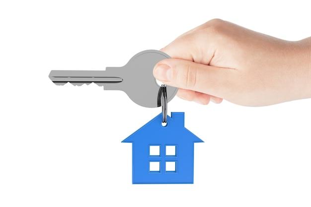Ludzka ręka trzyma klucz do domu na białym tle