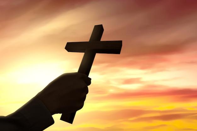Ludzką ręką trzyma krzyż chrześcijański