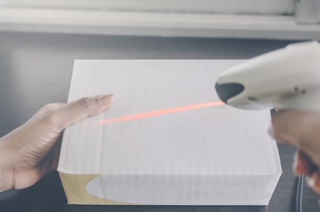 Ludzka ręka trzyma paczkę z czytnikiem kodów kreskowych do dostawy.