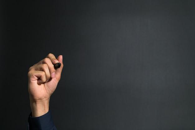 Ludzka ręka trzyma pióro w niebieskiej sukience