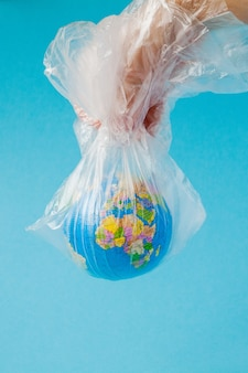 Ludzka ręka trzyma planetę ziemię w plastikowej torbie. pojęcie zanieczyszczenia odpadami z tworzyw sztucznych. globalne ocieplenie spowodowane efektem cieplarnianym.