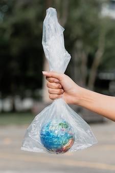 Ludzka ręka trzyma planetę ziemię w plastikowej torbie. pojęcie zanieczyszczenia odpadami z tworzyw sztucznych. globalne ocieplenie spowodowane efektem cieplarnianym