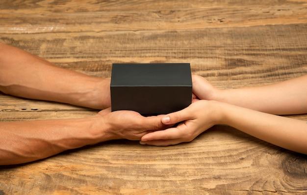 Ludzka ręka trzyma prezent, prezent, pudełko niespodzianka na białym tle na drewnianym tle. koncepcja celebracji, wakacji, rodziny, komfortu w domu, ferii zimowych, sylwestra, urodzin, rocznicy