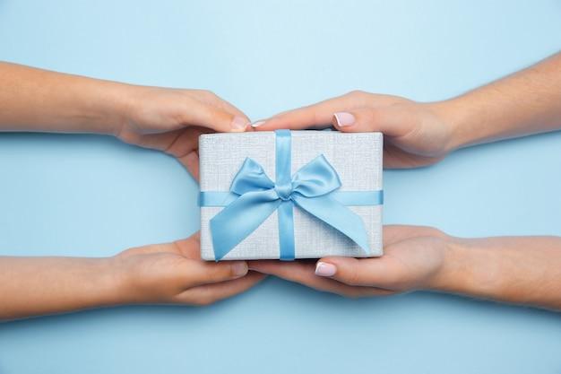 Ludzka ręka trzyma prezent, prezent, pudełko niespodzianka na białym tle na niebieskim tle. koncepcja celebracji, wakacji, rodziny, komfortu w domu, ferii zimowych, sylwestra, urodzin, rocznicy