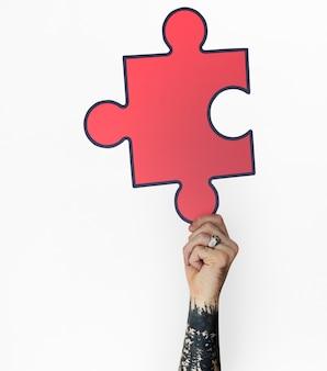 Ludzka ręka trzyma puzzle