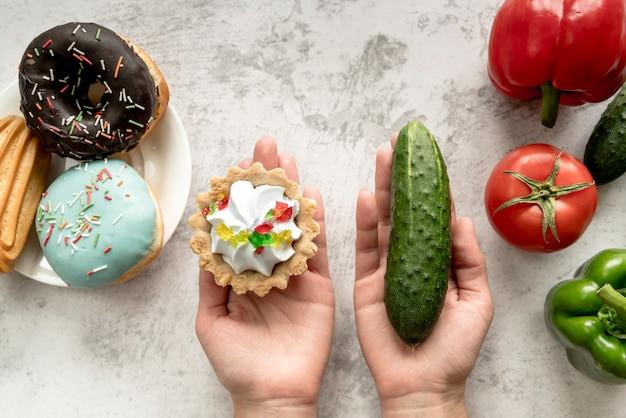 Ludzka ręka trzyma tarta tort i ogórek blisko warzyw i słodkiego jedzenia nad tłem