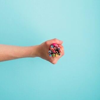 Ludzka ręka trzyma wiązkę kolorowi ołówki na błękitnym tle