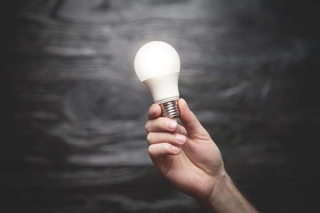 Ludzka ręka trzyma żarówkę na czarnym tle pojęcie kreatywności