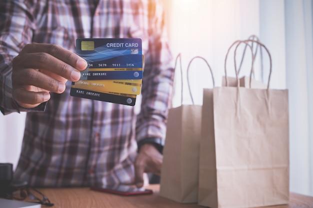 Ludzką ręką trzymaj karty kredytowe z papierowymi torebkami typu kraft