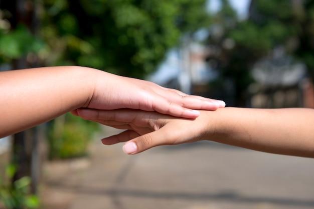 Ludzka ręka trzymająca drugą rękę z rozmytym tłem