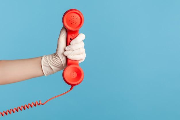 Ludzka ręka w białych rękawiczkach chirurgicznych, trzymając i pokazując słuchawkę słuchawki telefonu.
