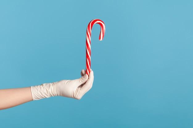 Ludzka ręka w białych rękawiczkach chirurgicznych trzymająca i pokazująca świąteczne paski czerwono-białej laski cukrowej