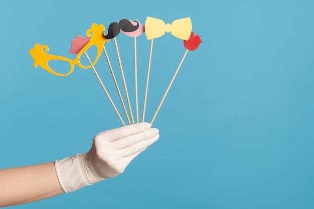 Ludzka ręka w białych rękawiczkach chirurgicznych trzymająca i pokazująca w dłoni wiele różnych fotobudek z kijem