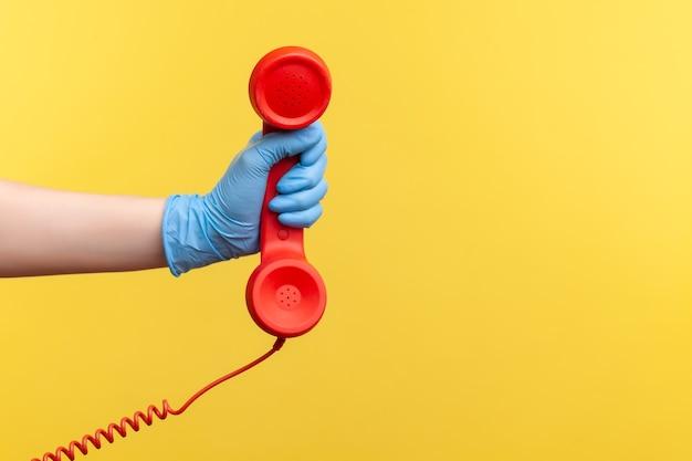 Ludzka ręka w niebieskich rękawiczkach chirurgicznych, trzymając i pokazując czerwony odbiornik słuchawki telefonu.