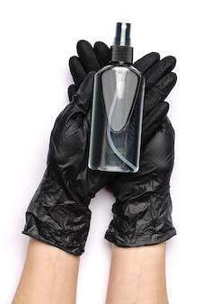 Ludzka ręka w rękawicy ochronnej, trzymając alkohol do dezynfekcji rąk w sprayu