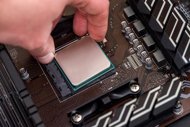 Ludzka ręka wyjmując procesor z płyty głównej