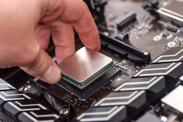 Ludzka ręka wyjmująca procesor z płyty głównej