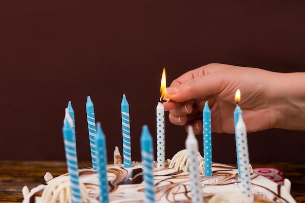 Ludzka ręka z zapałką, zapalająca świeczkę na torcie urodzinowym, na drewnianym biurku