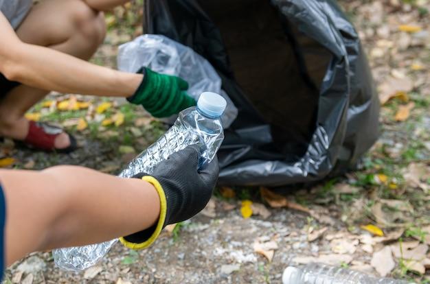 Ludzka ręka zbiera odpady z tworzyw sztucznych w workach na śmieci dla środowiska