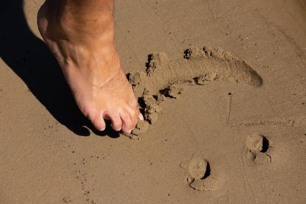 Ludzka stopa rysuje, uśmiech na piasku. uśmiechnij się na piasku na plaży.