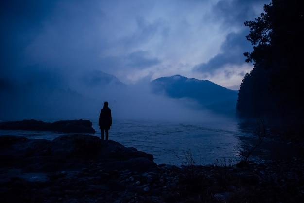 Ludzka sylwetka w niebieskiej mgle na tle gór i rzeki. gęsta mgła o wieczornym zmierzchu. tajemnicza atmosfera. pojęcie samotności, refleksji, medytacji.