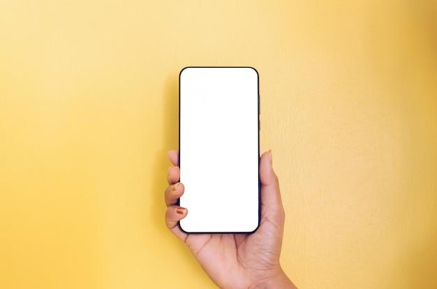 Ludzki ręki mienia smartphone z białym parawanowym tłem.