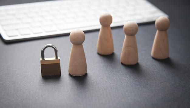 Ludzkie drewniane figurki z kłódką i klawiaturą komputerową.