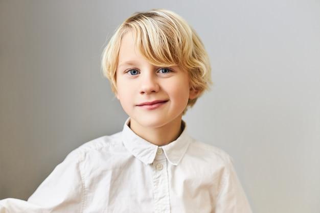 Ludzkie emocje, reakcje i uczucia. portret przystojny ładny uczeń o blond włosach i niebieskich oczach pozowanie na białym tle w białej koszuli