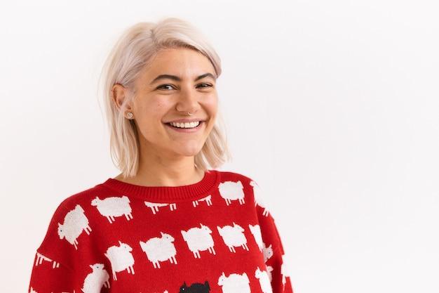 Ludzkie reakcje i uczucia. portret uroczej ładnej dziewczyny z kolczykiem w nosie pozuje w stylowym czerwonym swetrze z owieczkami na pustej białej ścianie, z radosnym promiennym uśmiechem