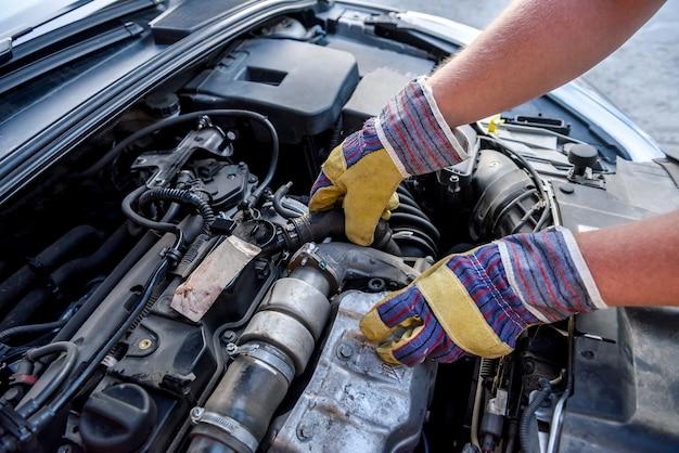 Ludzkie ręce badające silnik samochodu w rękawicach ochronnych z bliska