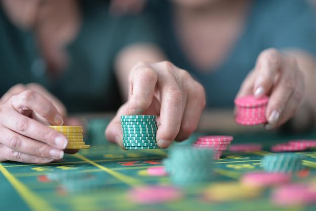 Ludzkie ręce bawiące się żetonami w kasynie z bliska