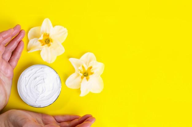 Ludzkie ręce biorą krem kosmetyczny w słoiku i kwitnących kwiatów na jasnym żółtym tle.